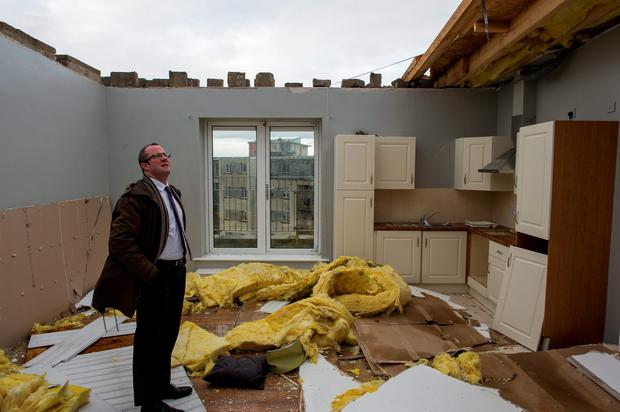 Reporter Conor Feehan surveys the damage to the apartment