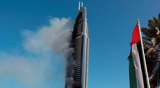 Smoke billows from the Address Downtown skyscraper in Dubai, United Arab Emirates today (AP Photo/Jon Gambrell)