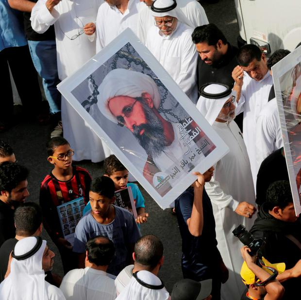 In this Saturday, May 30, 2015, photo, Saudis carry a poster demanding freedom for jailed Shiite cleric Sheikh Nimr al-Nimr, during a funeral procession. (AP Photo/Hasan Jamali)