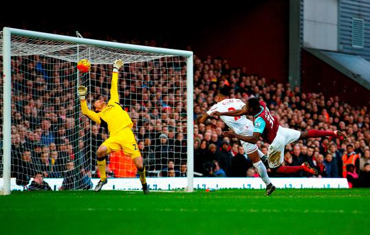 Michail Antonio (R) of West Ham United heads the ball past Simon Mignolet (L) of Liverpool to score his team's first goal during the Barclays Premier League match between West Ham United and Liverpool