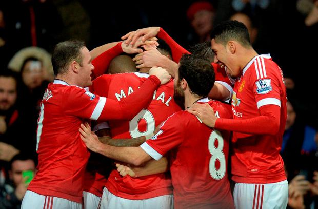 Manchester United's French striker Anthony Martial (C) is congratulated by teammates