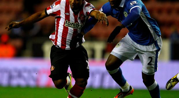 Stephane Sessegnon of Sunderland holds off Steve Gohouri of Wigan in 2012