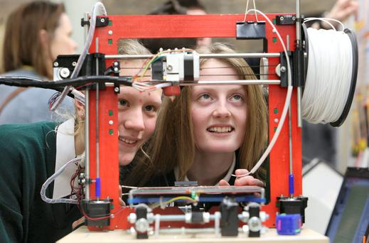 Martha Nic Ionais, (13) left, and Caoilfhionn Ni Dheorain (14), with their project, educating by making shapes with a 3D printer at the BT Young Scientist and Technology Exhibition at the RDS. Photo: Damien Eagers.