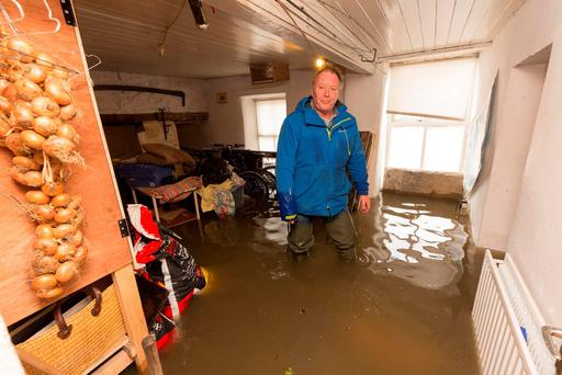 NO LAUGHING MATTER: Shem Caulfield, who owns the boat from which Joan Burton fell last Thursday, has to deal with flooding in his house situated on the Quays in Thomastown, Co Kilkenny. Photo: Dylan Vaughan