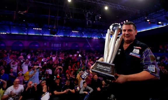 Gary Anderson celebrates with the Sid Waddell trophy after winning the final during day fifteen of the William Hill PDC World Championship at Alexandra Palace, London. Photo: Steve Paston/PA Wire.