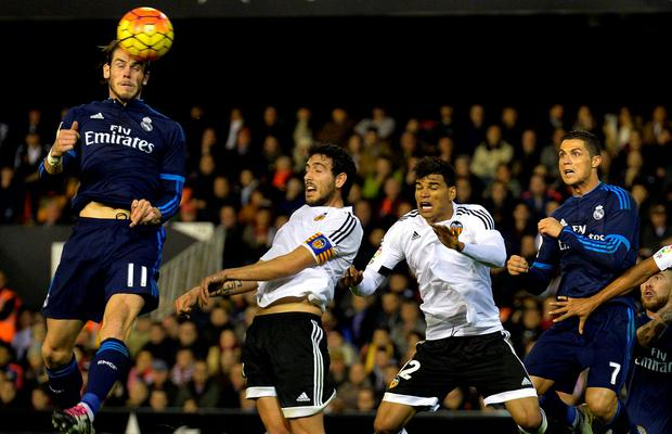 Real Madrid's Gareth Bale (l) heads the ball to score against Valencia at the Mestalla. Photo: Getty Images