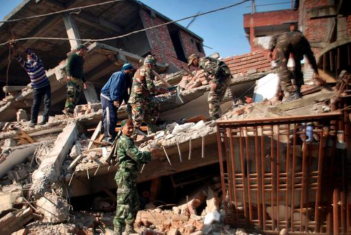 Indian soldiers and locals remove debris from a damaged building after an earthquake in Imphal, capital of the northeastern Indian state of Manipur, Monday, Jan. 4, 2016. A 6.7 magnitude earthquake hit India's remote northeast region before dawn on Monday. (AP Photo/Bullu Raj)