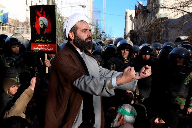 Surrounded by policemen, a Muslim cleric addresses a crowd during a demonstration to protest the execution of Saudi Shiite Sheikh Nimr al-Nimr, seen in poster, in front of the Saudi embassy in Tehran, Iran, Sunday, Jan. 3, 2016