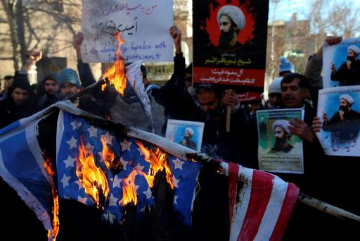 Iranian demonstrators burn representations of the U.S. and Israeli flags during a demonstration in front of the Saudi Arabian Embassy in Tehran, Iran, to protest the execution of Saudi Sheikh Nimr al-Nimr, a prominent opposition Shiite cleric, seen in posters, Sunday, Jan. 3, 2016