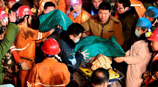 In this Dec. 25, 2015 photo released by China's Xinhua News Agency, a trapped miner is rescued from a collapsed gypsum mine in Pingyi County, east China's Shandong Province. Chinese rescuers pulled more than 10 workers to safety and located another workers who were trapped after a mine collapsed in the eastern province of Shandong, state media said Saturda
