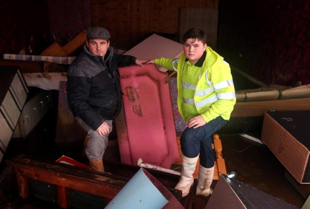Peter O'Brien and his son Patrick O'Brien, 14, inside their flood damaged shop on the day President Michael D Higgins visited flood damaged, Enniscorthy. Co. Wexford. Picture credit; Damien Eagers