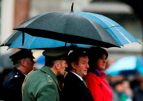 Taoiseach Enda Kenny with Tánaiste Joan Burton at the first event to mark the centenary of the 1916 Rising, as three flags that were flown on O'Connell Street during the rebellion were raised over Dublin Castle. Photo: Brian Lawless/PA