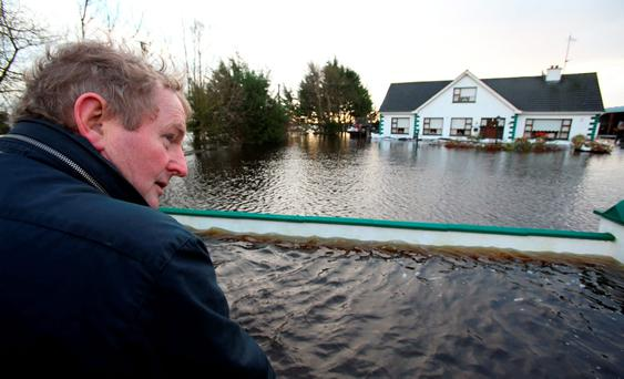 Taoiseach Enda Kenny outside the Dunning household before he visited following flooding in Carrickobrien, Ireland. Photo: Brian Lawless/PA Wire