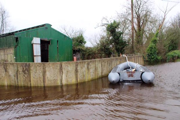 David Raleigh story An army inflatable boat tied up near a flooded farmyard in Springfield, Clonlara. Pic: Press 22