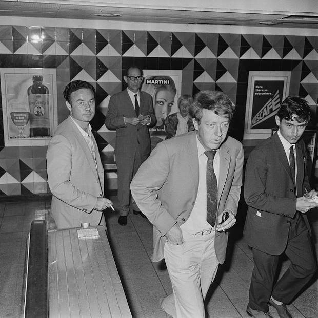 Business directors of NEMS (North End Music Stores) Robert Stigwood (centre) and David Shaw arriving at London Airport after hearing of the death of Brian Epstein, 28th August 1967. (Photo by George Stroud/Express/Hulton Archive/Getty Images)