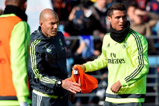 Real Madrid's Portuguese forward Cristiano Ronaldo (R) gives a bib to Real Madrid's new French coach Zinedine Zidane during his first training session