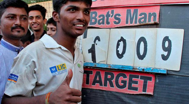 Schoolboy Pranav Dhanawade, 15, next to the scoreboard after his 1009 not out during an inter-school cricket tournament in Mumbai, India. Photo: REUTERS