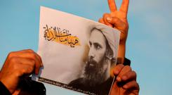 An Iraqi man holds a portrait of prominent Shiite Muslim cleric Nimr al-Nimr during a demonstration against his execution by Saudi authorities. AFP PHOTO / AHMAD AL-RUBAYEAHMAD AL-RUBAYE/AFP/Getty Images