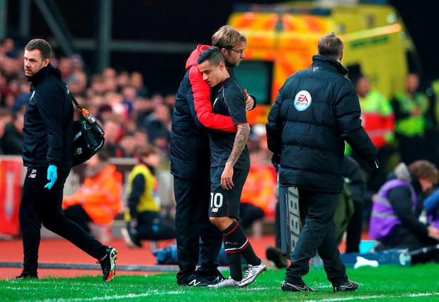Liverpool's Philippe Coutinho is embraced by manager Jurgen Klopp as he leaves the field with an injury during the Capital One Cup, semi final, first leg match at The Britannia Stadium, Stoke