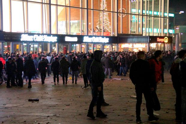 In this Dec. 31, 2015 picture, persons gather at the Cologne, Germany, main station. German police said Wednesday Jan. 6, 2016 that they are investigating whether a string of sexual assaults and thefts at New Year is linked to a known criminal network