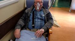 Patient James Coyle waits on a chair in Dublin's Beaumont Hospital