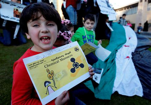 Syrian children carry placards as they call for the lifting of the siege off Madaya and Zabadani towns in Syria, in front of the offices of the U.N. headquarters in Beirut, Lebanon December 26, 2015. REUTERS/Jamal Saidi