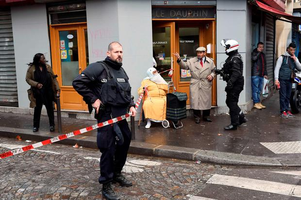 French police patrol near the Boulevard de Barbes in the north of Paris after police shot a man dead as he was trying to enter a police station in the nearby Rue de la Goutte d'Or Credit: LIONEL BONAVENTURE (AFP/Getty Images)