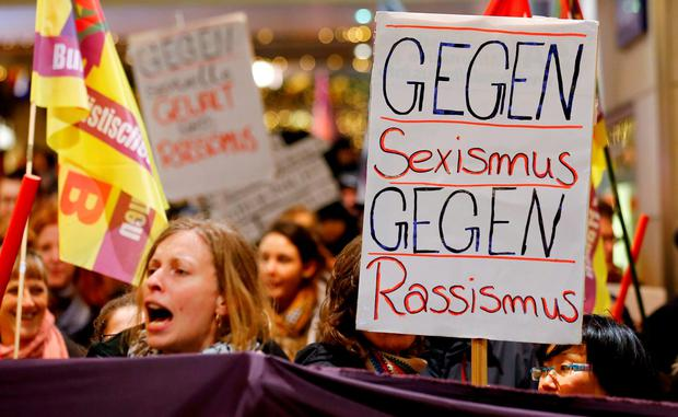Women shout slogans and hold up a placard that reads
