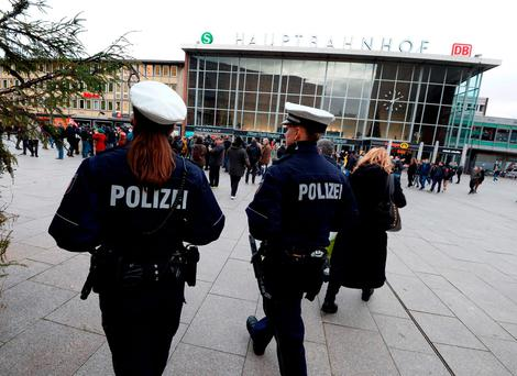 Police officers in front of the main train station and the Cathedral in Cologne where dozens of sexual assaults against women were reportedly carried out on New Year's Eve Credit: Roberto Pfeil (AFP/Getty Images)