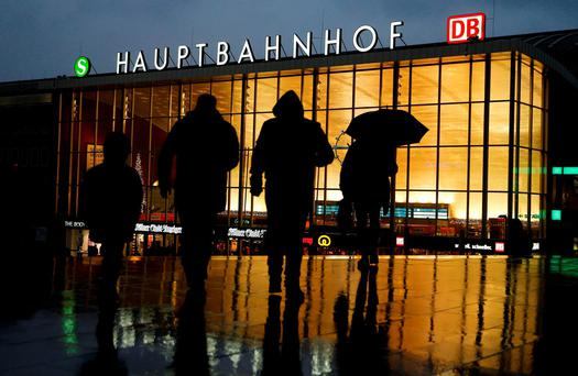 People walk in front of the main railway station in Cologne where many much of the New Year's Eve violence took place Credit: Reuters