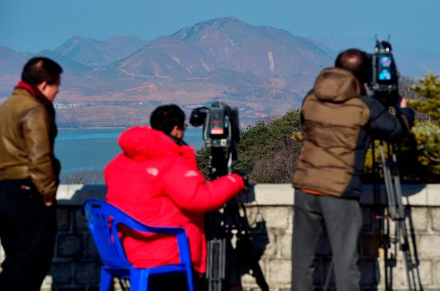 Cameramen film video footage of North Korea's border county of Kaepoong (background) from a South Korean observation post in Paju near the Demilitarized Zone dividing two Koreas on January 8, 2016.