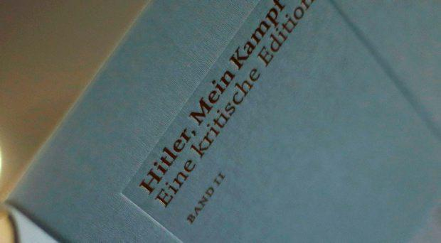 The owner of a book shop looks through a copy of the book 'Hitler, Mein Kampf. A Critical Edition' at his store in Munich, Germany January 8, 2016