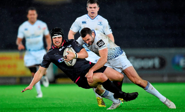 Dan Evans of the Ospreys is tackled by Rob Kearney, Picture credit: Stephen McCarthy / SPORTSFILE