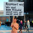 "Performance artist Milo Moire holds up a poster reading ""Respect us! We are no fair game, even when we are naked!!!"" as she stands near Cologne's landmark, the Cologne Cathedral, to protest on January 8, 2016 against offenses against women that happened in Cologne on New Year's Eve. Thirty-one suspects, including 18 asylum seekers, are under investigation over offences including assault and theft in Cologne on New Year's Eve, Germany's interior ministry said. / AFP / dpa / Oliver Berg / Germany OUTOLIVER BERG/AFP/Getty Images"