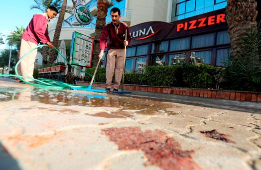 Cleaners try to clean blood stains near the entrance to Bella Vista Hotel in the Red Sea resort of Hurghada, Egypt, January 9, 2016. Two armed assailants attacked a hotel in the Egyptian Red Sea resort town of Hurghada on Friday, wounding three foreign tourists, Egyptian officials said
