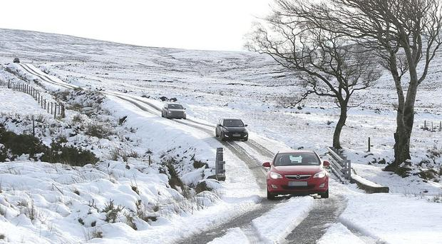 Cars negotiate a snow-covered Sally Gap in Wicklow