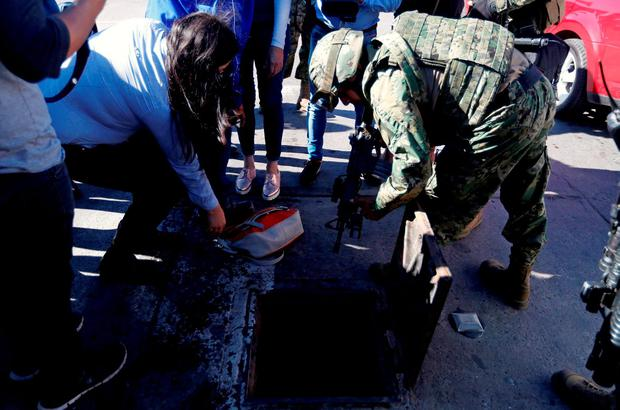 A soldier points his weapon to a entrance of a drain, from where Joaquin