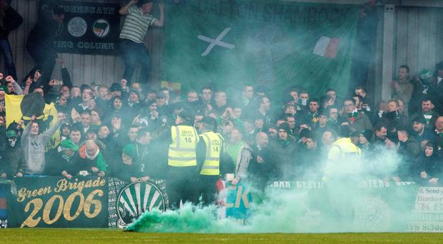 Flares on the pitch during the Scottish Cup, Fourth Round match at Stair Park, Stranraer.