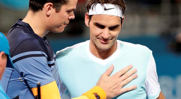 Milos Raonic of Canada, left, speaks to Roger Federer of Switzerland after winning the men's final match during the Brisbane International tennis tournament in Brisbane, Australia. Photo: Tertius Pickard/AP