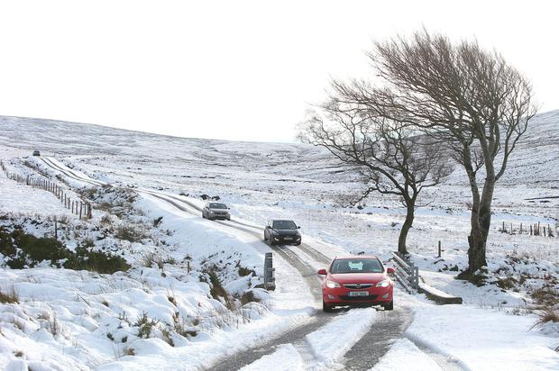 Cars drive across a snow-covered Sally Gap in Co Wicklow Photo: Damien Eagers