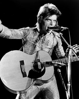 British rock singer David Bowie performs with an acoustic guitar on stage, in costume as 'Ziggy Stardust,' circa 1973. (Photo by Hulton Archive/Getty Images)