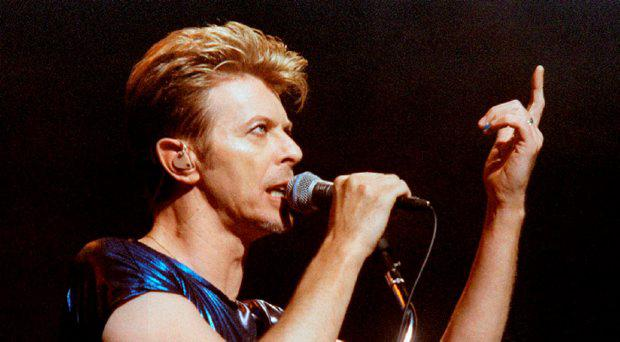 Singer David Bowie gestures as he performs one of the the first songs of a six-week concert tour of North America while appearing with the band Nine Inch Nails at the Meadows Music Theater in Hartford, Connecticut, in this September 14, 1995 file photo.