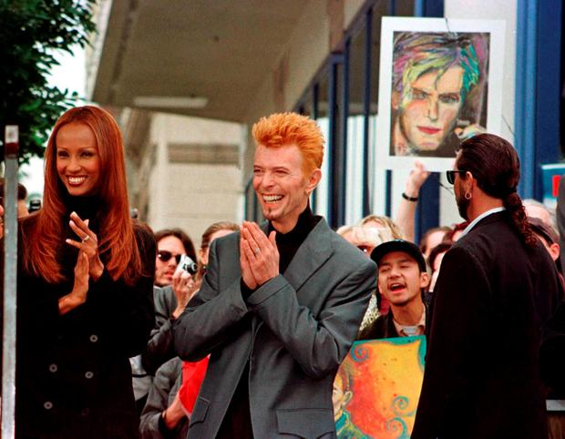 Rock singer David Bowie (R) is shown with his wife Iman (L) with a crowd of Bowie's fans behind them prior to ceremonies honouring Bowie with a star on the Hollywood Walk of Fame in this February 12, 1997 file photo. Singer Bowie has died after an 18-month battle with cancer, his official Twitter account announced on January 11, 2016