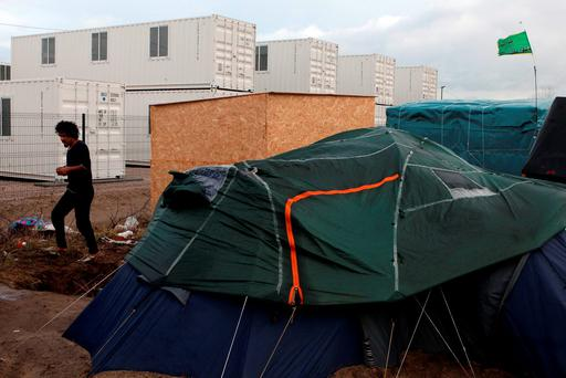 A man walks past containers, at rear, at the entrance of the Calais refugee camp, northern France (AP Photo/Michel Spingler)