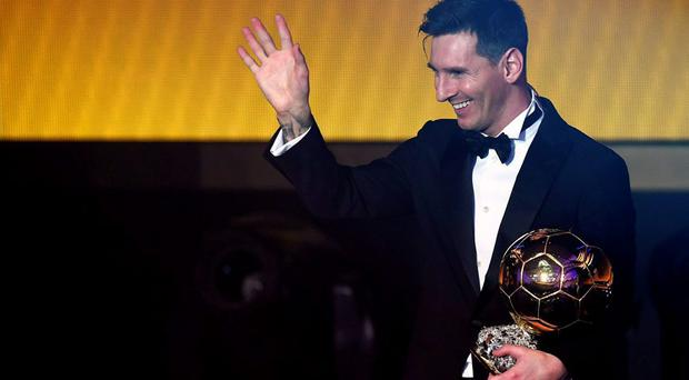 Lionel Messi waves holding his trophy after receiving the 2015 FIFA Ballon dOr award