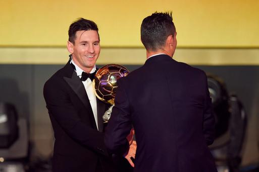 Lionel Messi of Argentina and FC Barcelona the winner of the Ballon d'or is congratulated by Cristiano Ronaldo of Portugal and Real Madrid during the FIFA Ballon d'Or Gala 2015 at the Kongresshaus