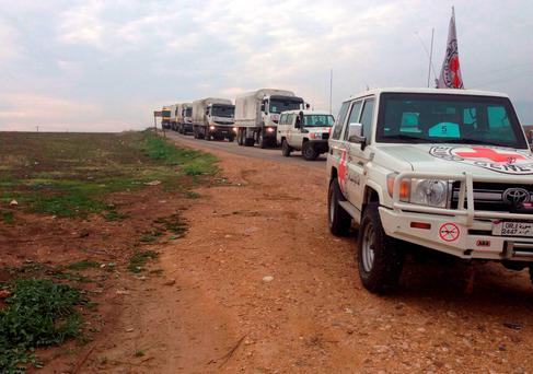 This picture provided by The International Committee of the Red Cross (ICRC), working alongside the Syrian Arab Red Crescent (SARC) and the United Nations (UN), shows a convoy containing food, medical items, blankets and other materials on its way to the towns of Foua and Kfarya in northern Syria. (ICRC via AP)