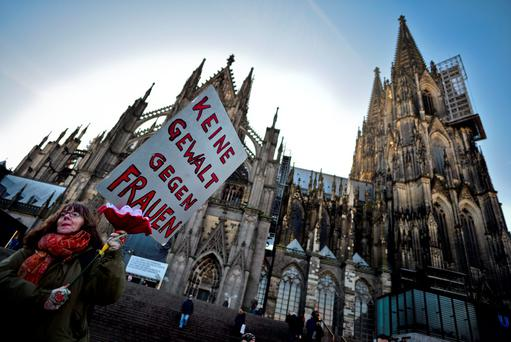 A woman holds up a sign saying 'No Violence Against Women' as protesters gather in front of Hauptbahnhof main railway station to protest against the New Year's Eve sex attacks on January 9, 2016 in Cologne, Germany. (Photo by Sascha Schuermann/Getty Images)