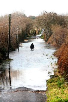 A resident walks through floods at Cleaheen Road in Roscommon. Photo: Brian Farrell