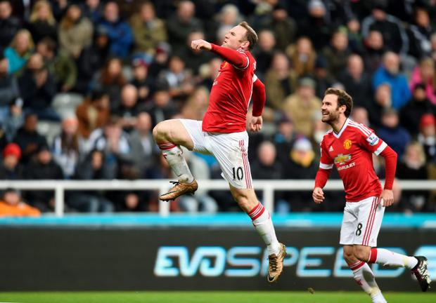 Wayne Rooney celebrates with Juan Mata as he scores their third goal during the Barclays Premier League match at St James' Park